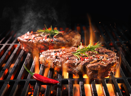 Beef steaks sizzling on the grill with flames