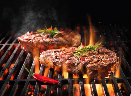 Steaks de boeuf grésillant sur le gril avec des flammes