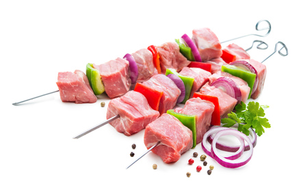 Kebabs - raw meat and vegetables on skewers, ready for grilling. Isolated on white
