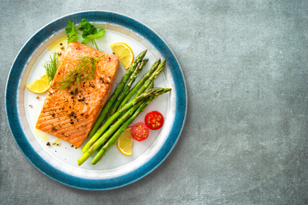 Grilled salmon steak garnished with green asparagus, lemon and tomatoes.Top view Stock Photo - 121174540