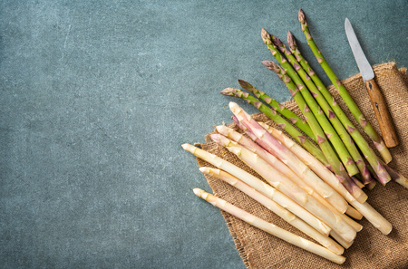 Green and white fresh asparagus on table