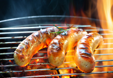 Delicious german sausages sizzling over the coals on barbecue grill Archivio Fotografico - 121174545