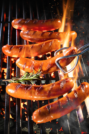 Delicious german sausages sizzling over the coals on barbecue grill Archivio Fotografico - 121174546