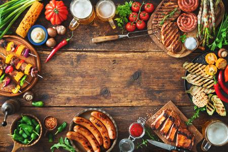 Barbecuemenu. Gegrild vlees en groenten op rustieke houten tafel met kopieerruimte voor tekst Stockfoto