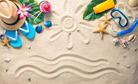 Straw hat with a exotic cocktail, sunglasses and other beach accessories on sand - summer holidays concept