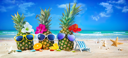 Attractive pineapples in stylish sunglasses on the sand beach against turquoise sea. Tropical summer vacation concept Фото со стока