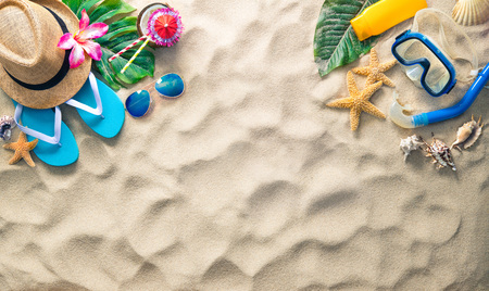 Straw hat with a exotic cocktail, sunglasses and other beach accessories on sand - summer holidays concept Archivio Fotografico - 121800564