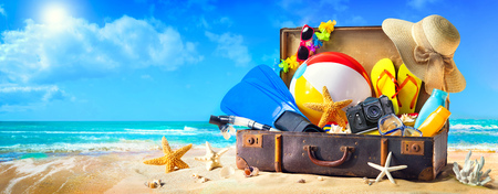 Preparation for summer vacation. Beach accessories in suitcase on sand. Family holidays concept Фото со стока