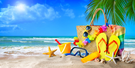 Tropical beach with sunbathing accessories, summer holiday background. Travel and beach family vacation