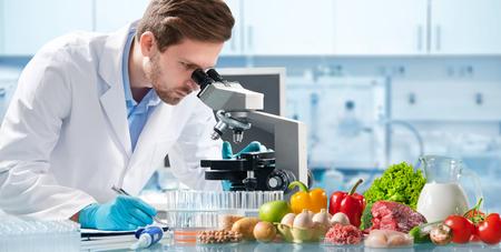 Voedselkwaliteitscontroledeskundige die specimens van kruidenierswaren in het laboratorium inspecteert Stockfoto