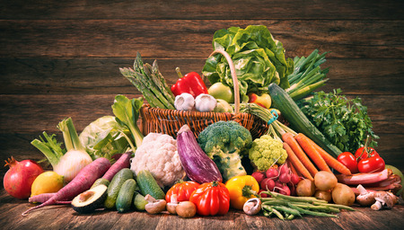 Assortment of fresh organic vegetables and fruits in wicker basket. Selection of organic food for healthy nutrition