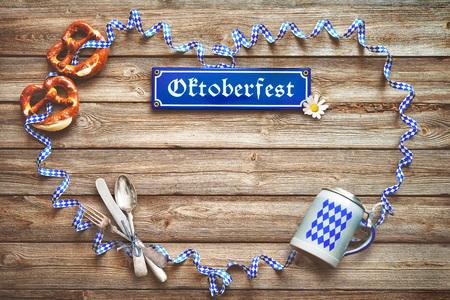 Rustic background for Oktoberfest with Bavarian white and blue streamer, pretzel, bier stein and silverware Stok Fotoğraf