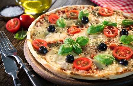 Italian pizza with mozzarella cheese, basil, black olives and cherry tomatoes