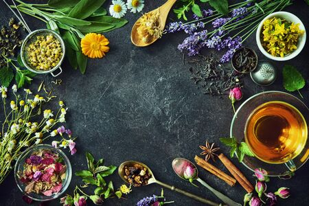 Cup of healthy herbal tea with mint, sage, cinnamon, dried rose, chamomile and lavender flowers on dark background. Top view 스톡 콘텐츠