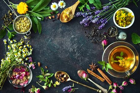 Cup of healthy herbal tea with mint, sage, cinnamon, dried rose, chamomile and lavender flowers on dark background. Top view