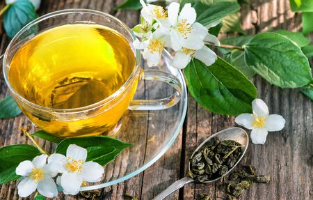 Cup of green tea with jasmine on wooden table