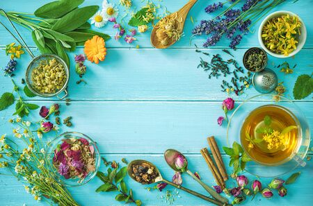 Cup of healthy herbal tea with mint, sage, cinnamon, dried rose, chamomile and lavender flowers on blue wooden table. Top view