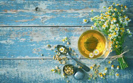 Filiżanka herbaty ziołowej z kwiatami rumianku na niebieskiej desce drewnianej w wieku. Zdrowy napój Zdjęcie Seryjne