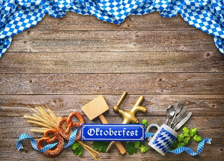 Rustic background for Oktoberfest with white and blue Bavarian fabric, wheat, hop, pretzel, beer tap and hammer Stock Photo