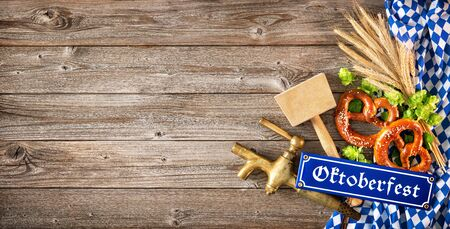Rustic background for Oktoberfest with white and blue Bavarian fabric, wheat, hop, pretzel, beer tap and hammer 스톡 콘텐츠