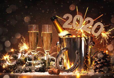 Fondo de celebración de Nochevieja con par de flautas y botella de champán en balde y una herradura como amuleto de la suerte