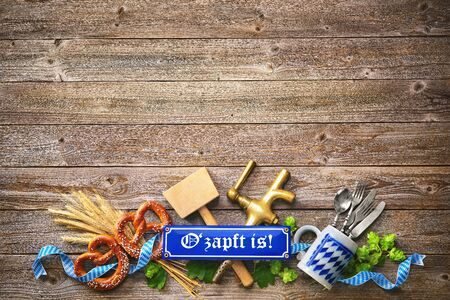 "Rustic background for Oktoberfest with letters O'zapft is! - translation: ""The beer is tapped"", white and blue Bavarian fabric, beer glass, hop, pretzel, beer tap and hammer"