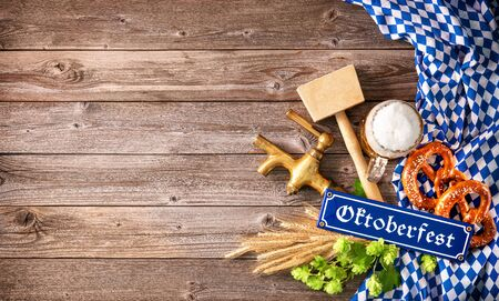 Rustic background for Oktoberfest with white and blue Bavarian fabric, beer glass, wheat, hop, pretzel, beer tap and hammer