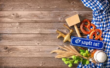 Rustic background for Oktoberfest with letters Ozapft is! - translation: The beer is tapped, white and blue Bavarian fabric, beer glass, hop, pretzel, beer tap and hammer