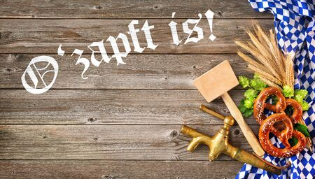 Rustic background for Oktoberfest with letters Ozapft is! - translation: The beer is tapped, white and blue Bavarian fabric, hop, pretzel, beer tap and hammer