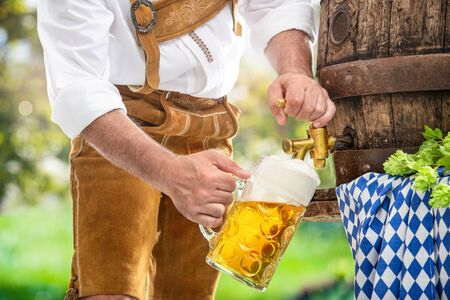 Bavarian man in leather trousers is pouring a large lager beer in tap from wooden beer barrel in the garden. Background for Oktoberfest, folk or beer festival
