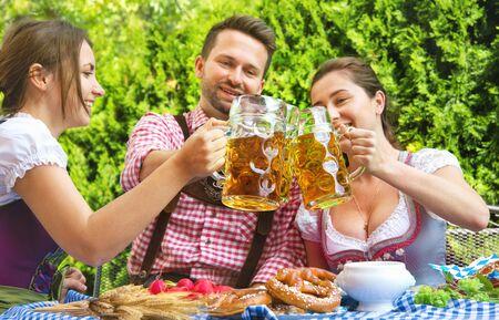 Junge Leute in Tracht, Dirndl und Lederhose haben Spaß im Biergarten in Bayern, Deutschland Bavaria Standard-Bild