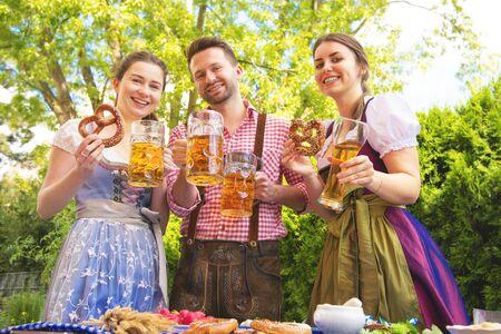 Les jeunes de Tracht, Dirndl et Lederhosen s'amusant dans le jardin de la bière en Bavière, Allemagne Banque d'images