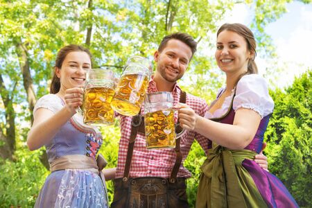 Young people in Tracht, Dirndl and Lederhosen having fun in Beer garden in Bavaria, Germany