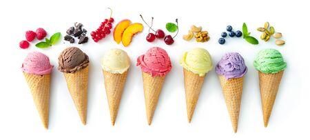 Varias variedades de helado en conos con menta, arándano, fresa, pistacho, cereza y chocolate aislado sobre fondo blanco.