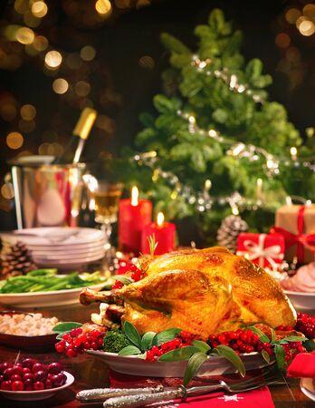 Truthahn-Weihnachtsessen. Gebackener Truthahn garniert mit roten Beeren und Salbeiblättern vor Weihnachtsbaum und brennenden Kerzen Standard-Bild