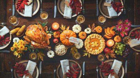 Thanksgiving celebration traditional dinner. Roasted turkey garnished with cranberries on a rustic style table decoraded with pumpkins, vegetables, pie, flowers and candles. Festive table setting