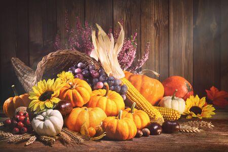 Joyeux Action de Graces. Corne d'abondance décorative avec citrouilles, courges, fruits et feuilles tombantes sur une table en bois rustique