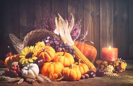 Felice Ringraziamento. Cornucopia decorativa con zucche, zucca, frutta e foglie che cadono su tavola in legno rustico