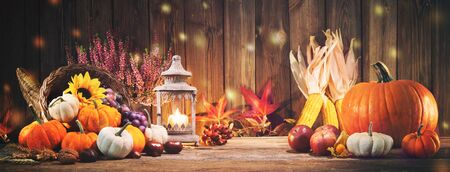 Happy Thanksgiving. Decorative cornucopia with pumpkins, squash, fruits and falling leaves on rustic wooden table