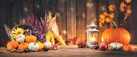 Happy Thanksgiving. Decorative cornucopia with pumpkins, squash, fruits and falling leaves on rustic wooden table Banco de Imagens