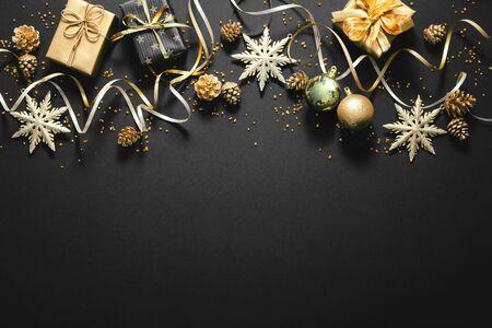 Decoración navideña dorada con cajas de regalo en la oscuridad.