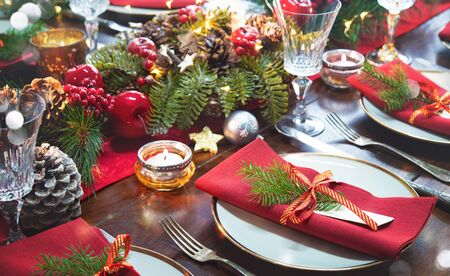 Christmas holidays table setting concept - wine glasses and tableware for festive dinner at home