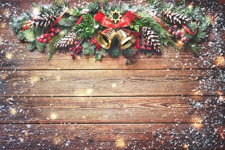 Background with Christmas bells, fir tree, pine cones and decoration on dark wooden board Stock Photo