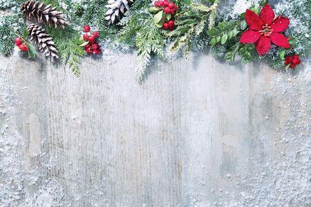 Weihnachts- und Neujahrshintergrund mit Tannenzweigen, Stechpalme und Schneefall auf weißem Holzbrett