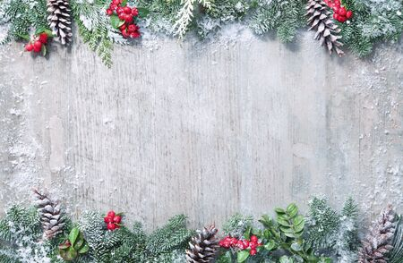 Christmas and New Year background with fir branches, holly and snowfall on wooden white board 写真素材