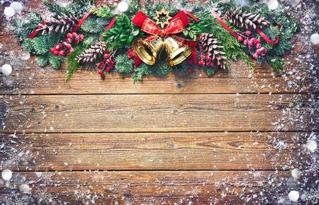 Background with Christmas bells, fir tree, pine cones and decoration on dark wooden board 版權商用圖片