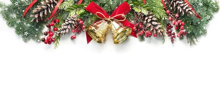 Decoration from snowy pine branches, cones, holly and Christmas bells isolated on white