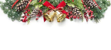 Dekoration aus verschneiten Tannenzweigen, Zapfen, Stechpalme und Weihnachtsglocken isoliert auf weiß