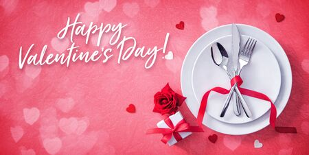 Red table setting cutlery with hearts decoration, gift box and rose for valentines days dinner