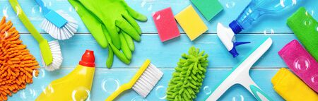 Colorfull cleaning items on blue wooden planks with the soap bubbles